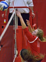 Canton's Kassie Tanana (right) goes up at the net Tuesday against Novi.