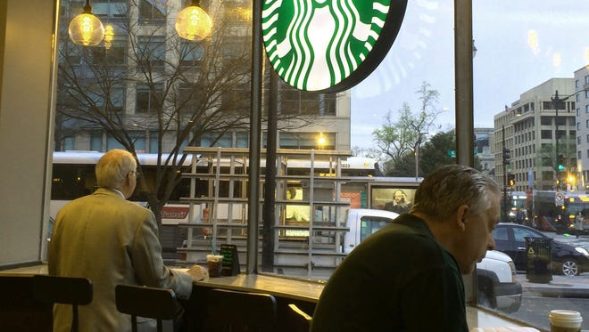 Patrons have morning coffee at a Starbucks in Washington on March 23, 2016. Starbucks announced several new products that expands the company's presence outside of its cafes, including a prepaid rewards Visa card, single-serve cold brew bottles and latte coffee pods.