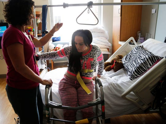 Kelsey Cummings practices standing during physical therapy in her Cedar Rapids hospital room March 24. She was impaled by a pole in a car accident in early March. It destroyed a hip joint, broke her pelvis and caused nerve damage.
