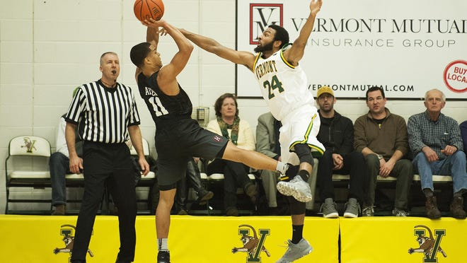 Vermont's Dre Wills (24) tries to block the shot by Harvard's Bryce Aiken (11) during the men's basketball game between the Harvard Crimson and the Vermont Catamounts at Patrick Gym on Monday night.
