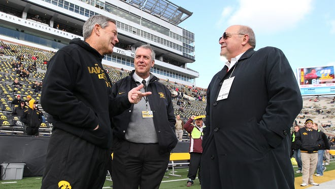 Iowa football coach Kirk Ferentz, left, and athletic director Gary Barta talk with Wisconsin athletic director Barry Alvarez on Nov. 2, 2013, at Kinnick Stadium in Iowa City.