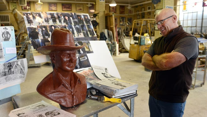 Artist Alan Cottrill stands next to reference materials and a sculpted bust of William Boyd as fictional cowboy Hopalong Cassidy from his studio in downtown Zanesville. Cottrill was commissioned to create the bust of the Ohio native celebrity for Laura Bates, who founded the Hopalong Cassidy festival in Cambridge.