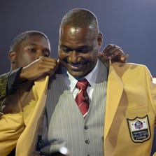 Derrick Brooks receives gold jacket from son Decalon Brooks at the 2014 Pro Football Hall of Fame Enshrinees gold jacket dinner at Canton Memorial Civic Center.
