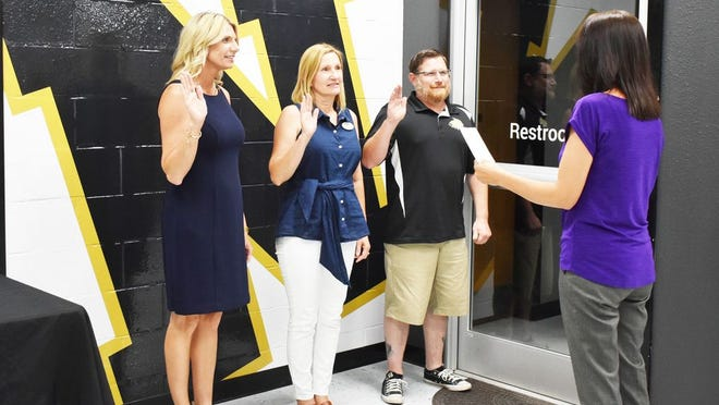 Three people were elected to 3-year terms on the Neosho Board of Education in the June elections. Left to right are Melissa Wright, new board member, Kim Wood, incumbent, and David Steele, incumbent. Tonya Patterson, executive administrative assistant is shown swearing them into office.