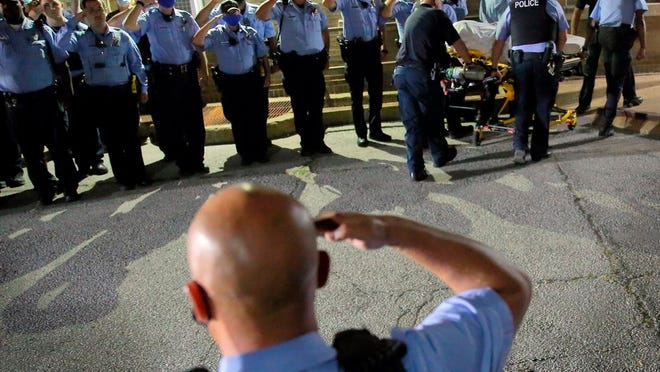 St. Louis police officers line up and salute as the body of fallen Officer Tamarris L. Bohannon is brought to the morgue in St. Louis, Sunday, Aug. 30, 2020. Bohannon died Sunday after being shot in the head by a barricaded gunman on the city's south side, authorities said.