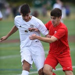 From left, Arlington's Eric Layden gains control of the ball ahead of Roy C. Ketcham's Mitchell Kuehner during Wednesday's game at Arlington High School.