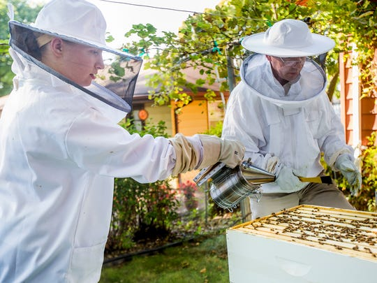 Clare Heinrich, 17, of Urbandale, and her father, Kurt, check on her beehive in the backyard of their Urbandale home on Tuesday, Sept. 20, 2016. Heinrich won a scholarship from the Iowa Honey Producer Association, which funded her to get the hives. The city of Urbandale says the hive has to be moved.