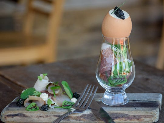 A farm egg with smoked trout and country ham custard served at Harvest, at 624 E. Market St.
