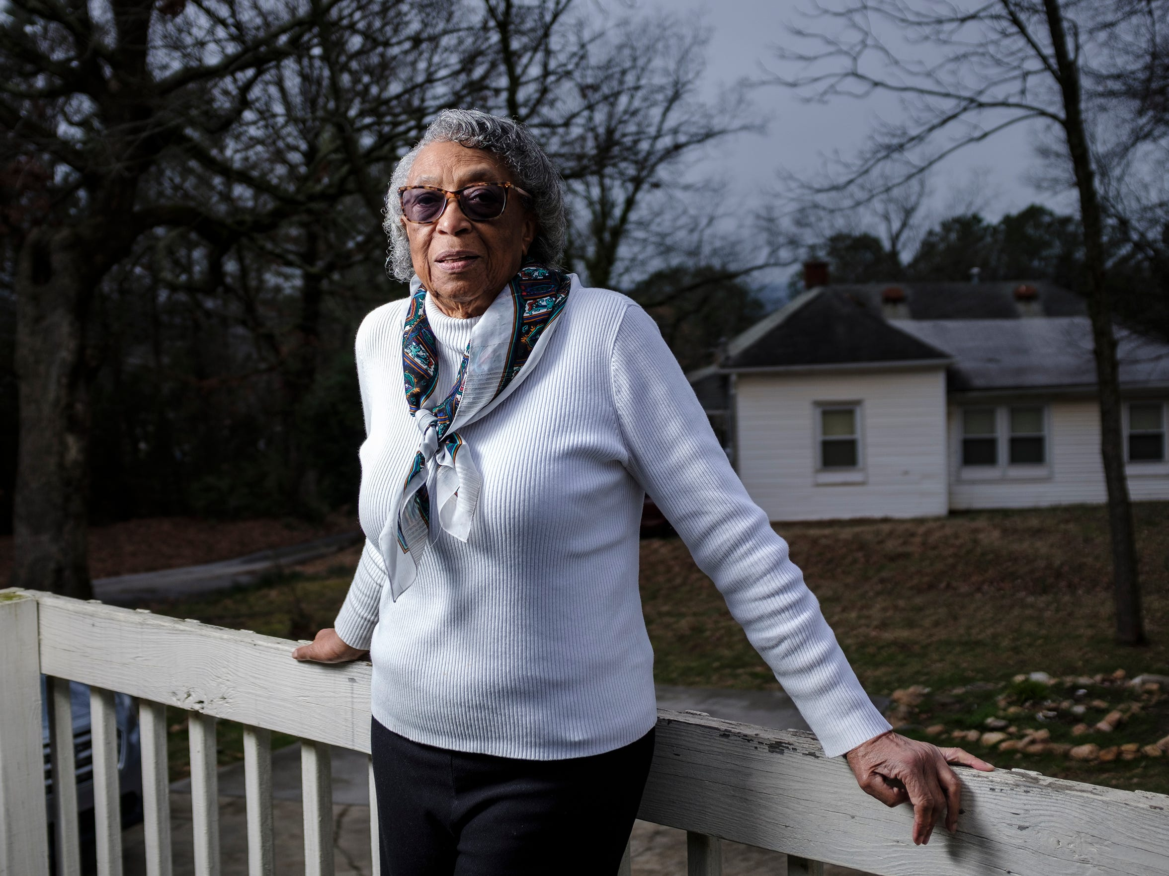 """Dorothy Jones stands on her porch in the Calhoun neighborhood in the city of Clemson. Jones lives adjacent to the home she grew up in and where her sister Ann Warren currently lives. Jones fears she will be the last in her generation where she lives to try to keep the land, but she vows to be there until """"my last breath."""""""