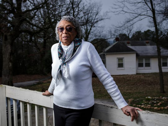 "Dorothy Jones stands on her porch in the Calhoun neighborhood in the city of Clemson. Jones lives adjacent to the home she grew up in and where her sister Ann Warren currently lives. Jones fears she will be the last in her generation where she lives to try to keep the land, but she vows to be there until ""my last breath."""