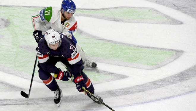 U.S. player Dylan Larkin, front, and Italy's Luca Frigo challenge for the puck during the Ice Hockey World Championship group A match at the Lanxess Arena in Cologne, Germany, Wednesday, May 10, 2017.