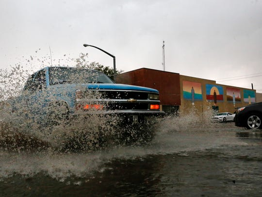 A driver splashes water while driving through a puddle