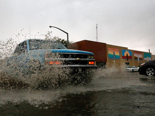 A driver splashes water while driving through a puddle on West Main Street in downtown Farmington Friday afternoon.