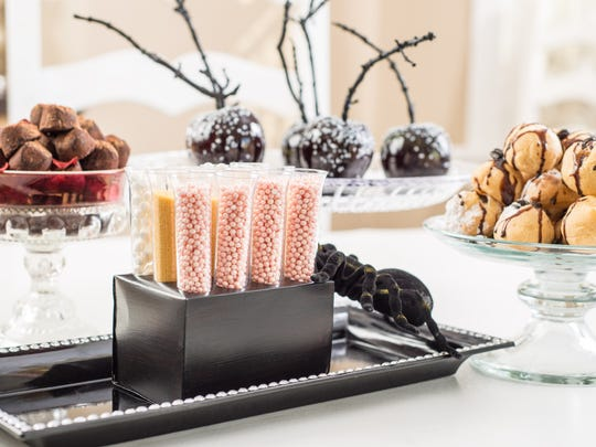 """Dawn Tavares and her crew from Cherry Bomb Catering are sending out (clockwise from left) chipotle chocolate truffles, glossy black """"arsenic"""" candy apples, mocha cream puffs, and sweet and savory pixie dust shooters at Fantasies in Chocolate."""