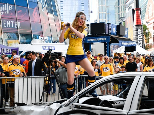Brittney Redden takes a swing on the smash car before game 3 of the Western Conference finals at the Bridgestone Arena in Nashville, Tenn., Tuesday, May 16, 2017.
