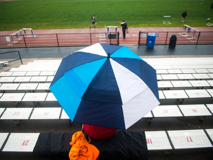A spectator watches the meet under cover of an umbrella