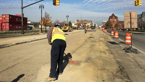 A construction worker brushes off debris on the M1-Line on Woodward Ave in Detroit,.  Officials are working to minimize the effects of light rail construction in Detroit on the city's annual Thanksgiving Day parade. Three locations along the Woodward Avenue route will narrow so the parade can move past heavy construction areas for the M-1 Rail project.