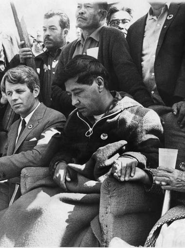 Cesar Chavez, farm labor leader, eats a piece of bread to end his 25-day fast at Delano, Calif., March 11, 1968. About 4,000 farm workers joined him in a symbolic bread-breaking ceremony marking the end of their leader's fasting for the principle of non-violence. With him are Sen. Robert F. Kennedy who came from Washington to take part and Chavez' wife, left, and mother. (AP Photo/Fresno Bee, Richard Darby) MANDATORY CREDIT