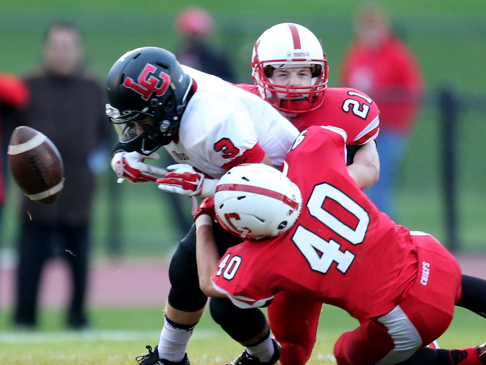 Livonia Churchill's Dylan Padget fumbles after being hit by Canton's Jacob Stephan on Oct. 3, 2014.