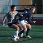 Junior Courtney Knoerl (left) defends the Farmington end of the field.