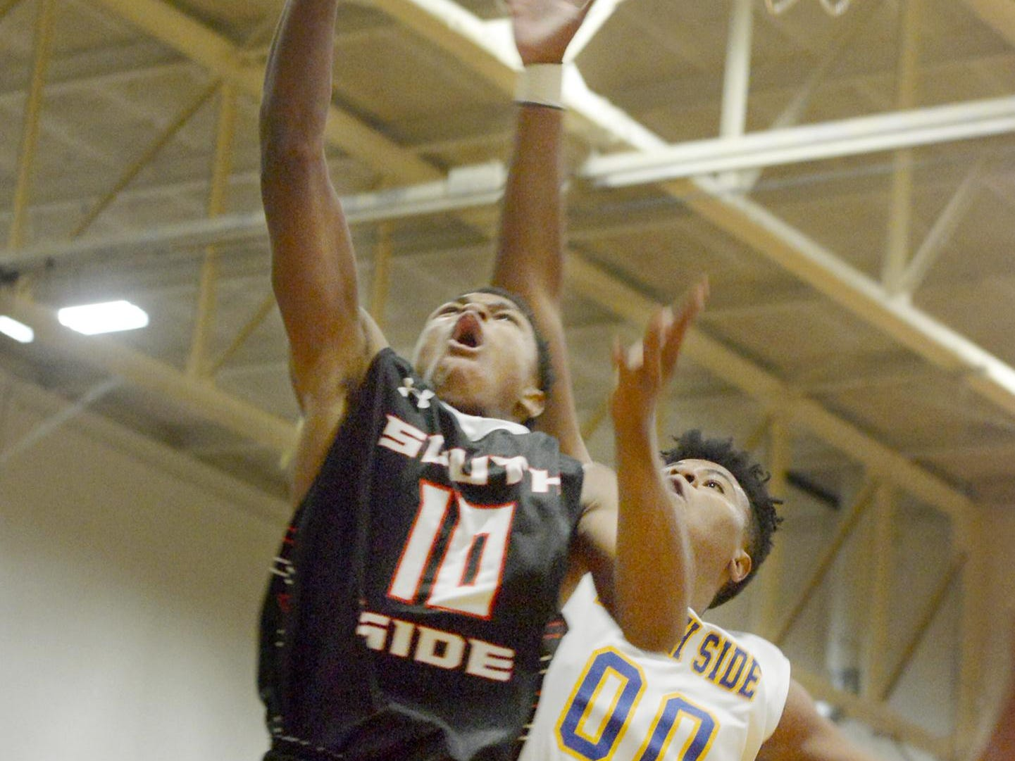 South Side's Keyon Jones goes up for a layup as North Side's Diego Womack attampts block his shot during their game, Tuesday evening at North Side. South Side defeated North Side, 87-52.