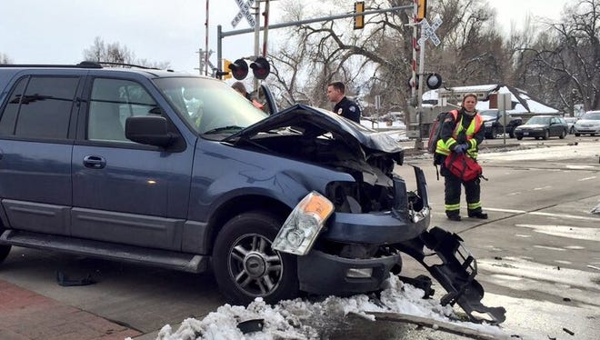 An SUV was left mangled at the intersection of Harmony Road and Mason Street after it ran a red light and hit the side of a MAX bus. Nobody was injured in the wreck.