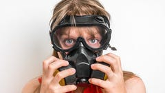 Young business woman with gas mask isolated on white.