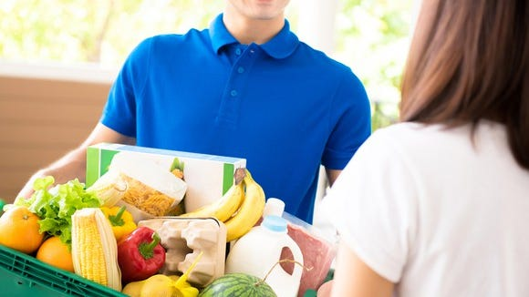 A smiling man delivers a tub full of groceries to a woman.