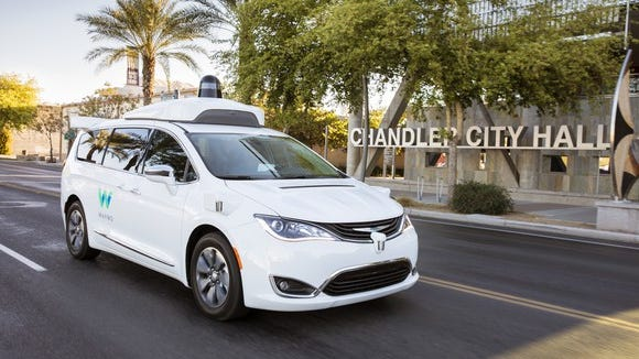 A white Chrysler Pacifica Hybrid minivan with Waymo markings and visible self-driving sensors on a public road