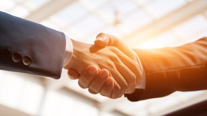 Close-up on a handshake between two men in business suits.