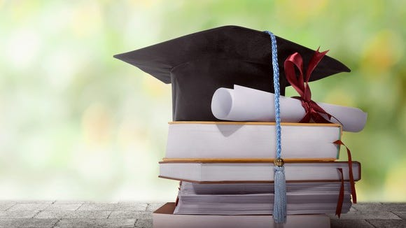 College graduation cap and rolled up degree sitting atop a stack of books