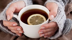 A lady's hands holding a cup of tea with a whole lemon slice in cup.