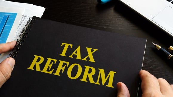 Notebook with Tax Reform written on the cover in yellow lettering.