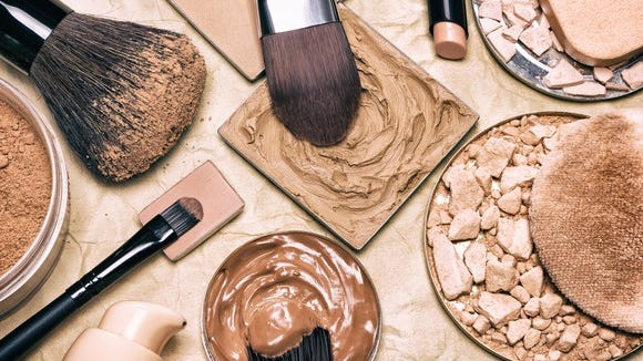 Close-up of an assortment of cosmetics products and brushes