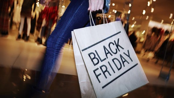 A person walking while holding a shopping bag labeled Black Friday