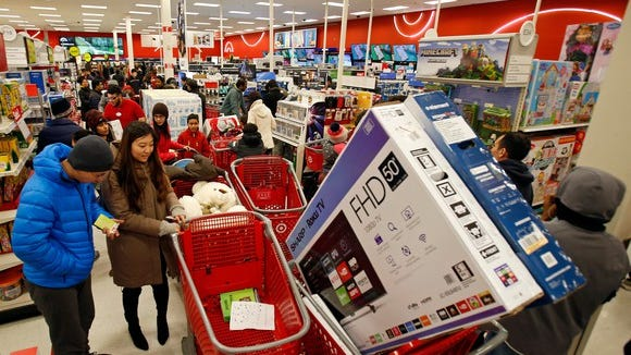 Shoppers line up at Target on Black Friday while once has a shopping cart with a big-screen TV in it.
