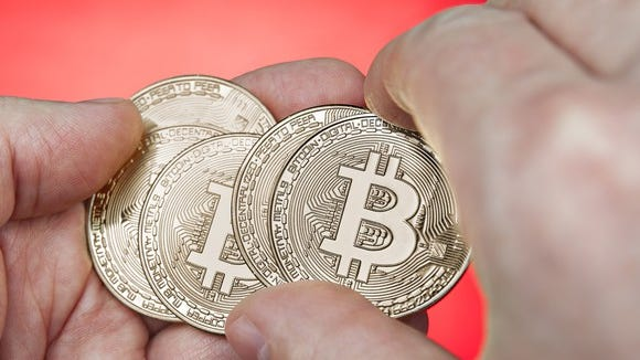 five golden bitcoins in someone's palm