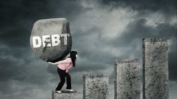 A person carrying a boulder up granite stairs. The bounder has the word debt written on it.