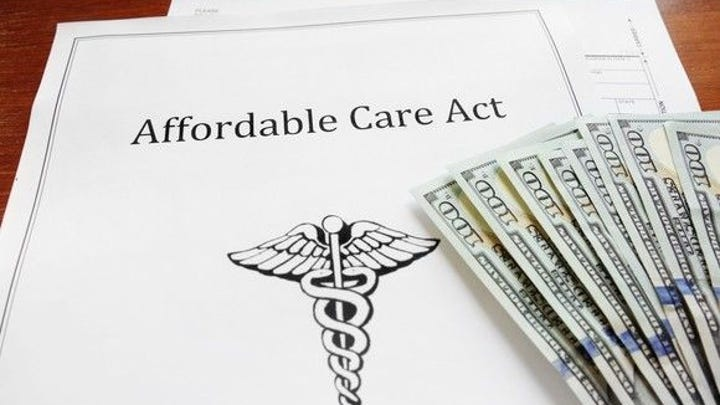 Report labeled Affordable Care Act with medical symbol and $100 bills, on a wood desk.