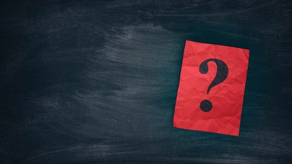 A red question mark sitting on a black chalkboard.