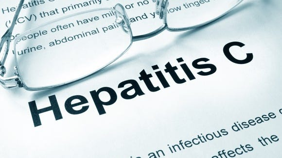 Eye glasses on a paper with the definition of hepatitis C
