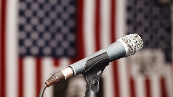Microphone in front of two American flags.