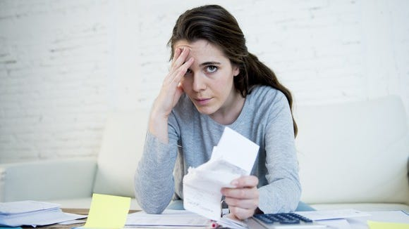 Woman holding her head while going through papers