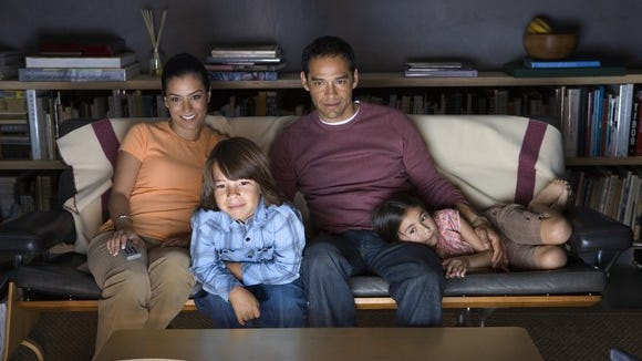 A family watches TV on a couch.