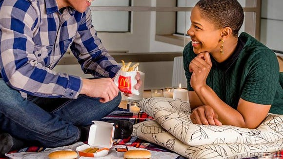 Two people eating McDonald's food.