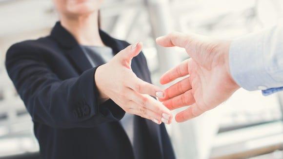 Businesswoman extends her hand for a handshake.