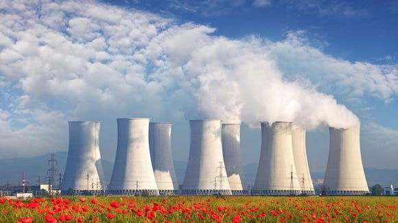 Nuclear power plants in the distance beyond a field of flowers