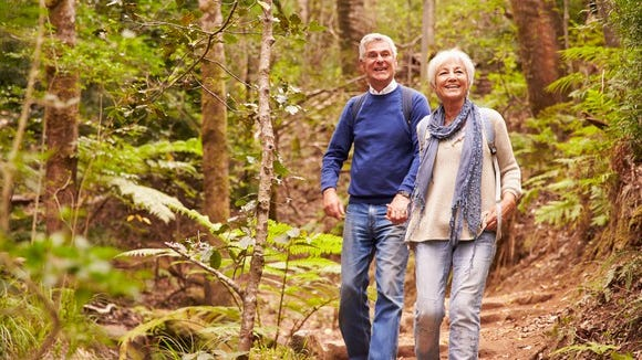 A senior man and woman holding hands while hiking