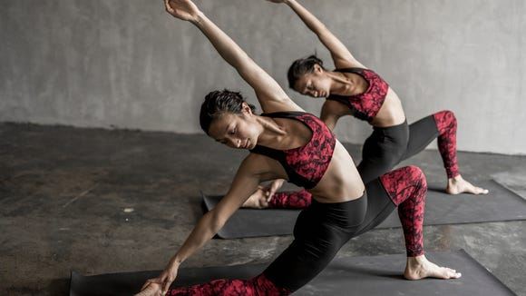 Two women practicing yoga and wearing Lululemon clothes.
