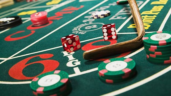 Craps table with dice showing 7, croupier stick, and varies pass line, field, and come bets shown.